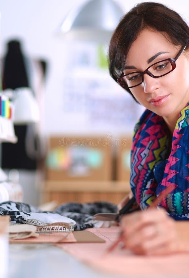 Damenschneiderin, die Kleidungsmuster auf Papier entwirft lizenzfreie stockbilder
