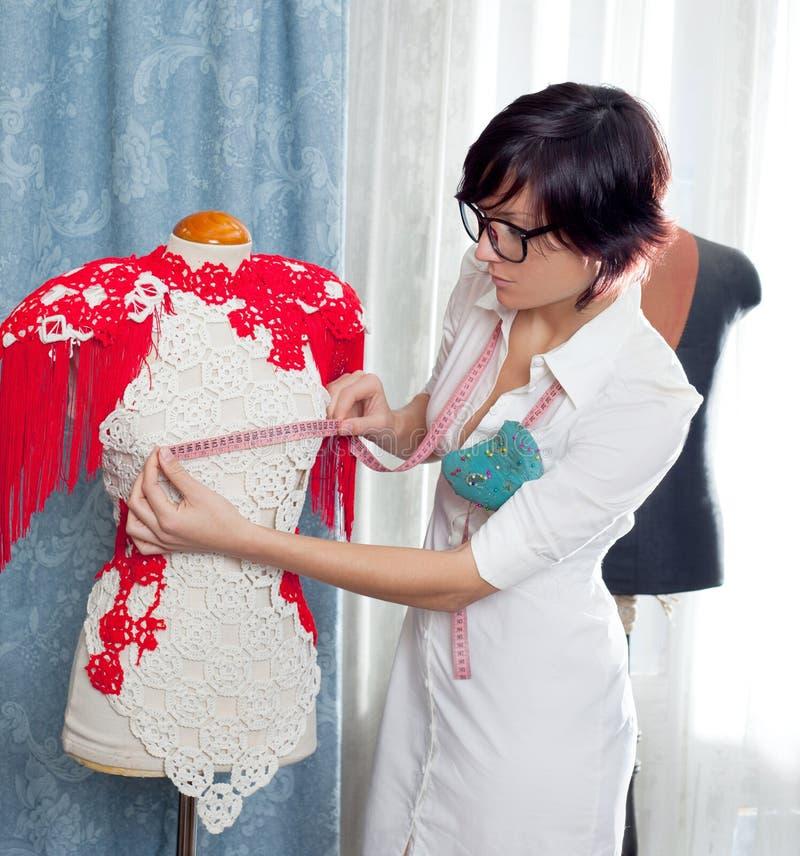 Damenschneiderin mit dem Mannequin, das zu Hause arbeitet lizenzfreies stockbild