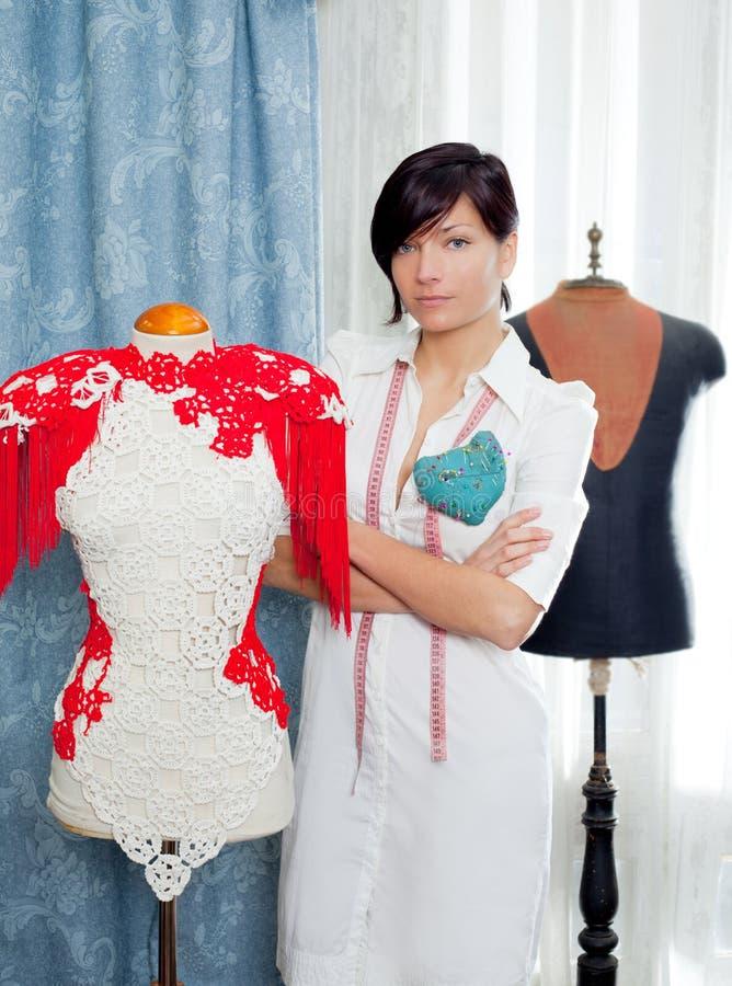 Damenschneiderin mit dem Mannequin, das zu Hause arbeitet stockbild
