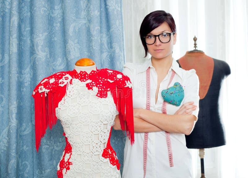 Damenschneiderin mit dem Mannequin, das zu Hause arbeitet stockfotografie