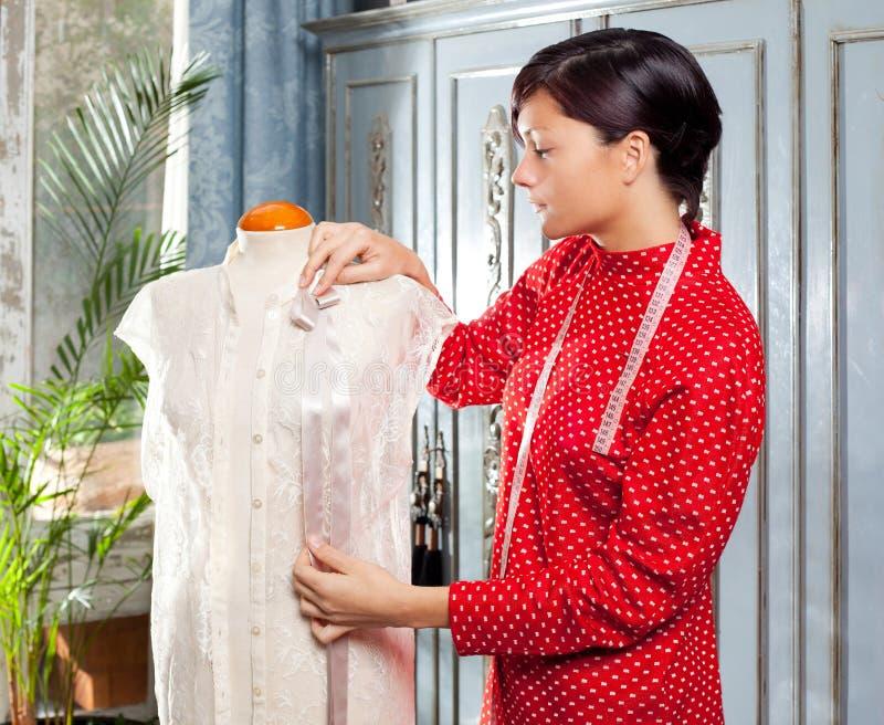 Damenschneiderin mit dem Mannequin, das zu Hause arbeitet stockfoto