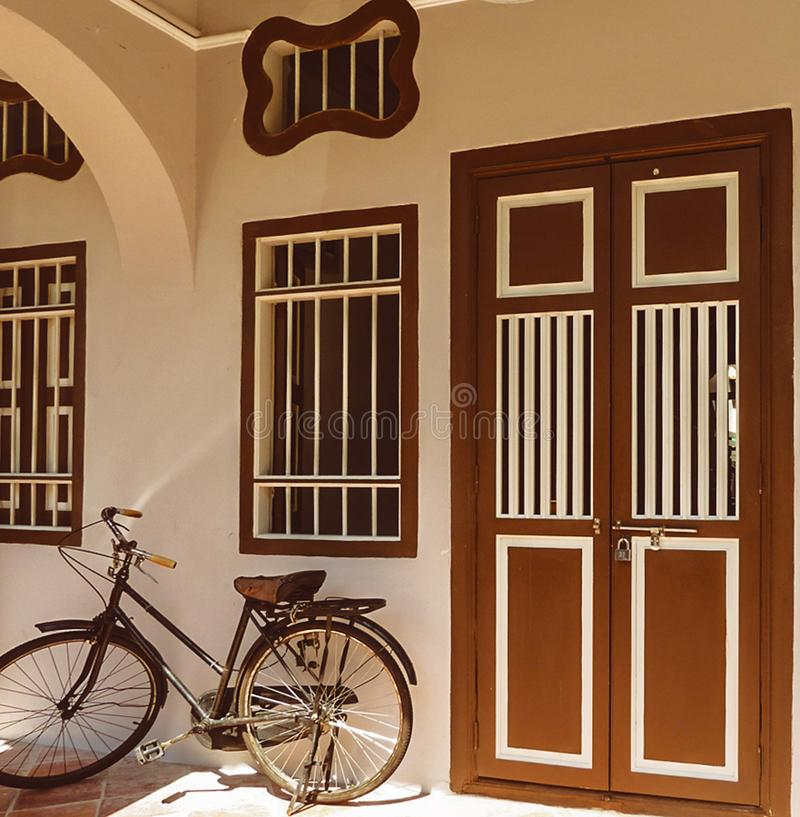 Damenstoßfahrrad, das neben Tür stillsteht lizenzfreies stockfoto