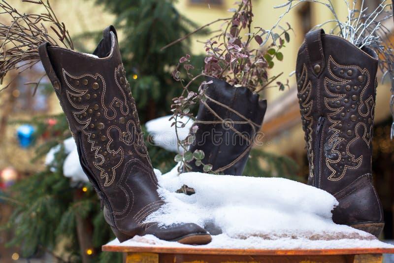 Damenweinleseleder-Cowboyschuhe bedeckt mit Schnee stockfotografie