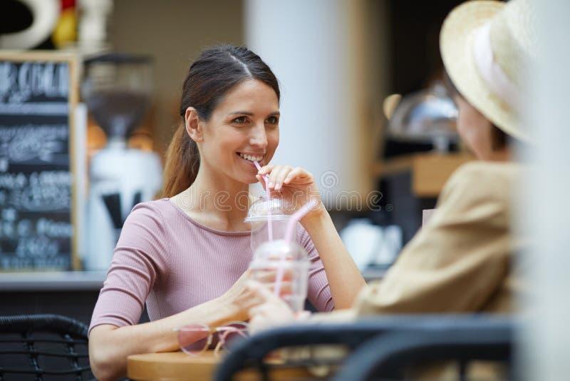 Damer som dricker förnyande drycker arkivfoto