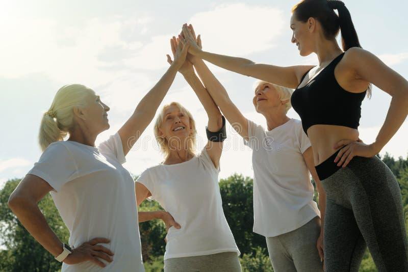 Dames supérieures et leur fiving élevé d'entraîneur après séance d'entraînement images libres de droits