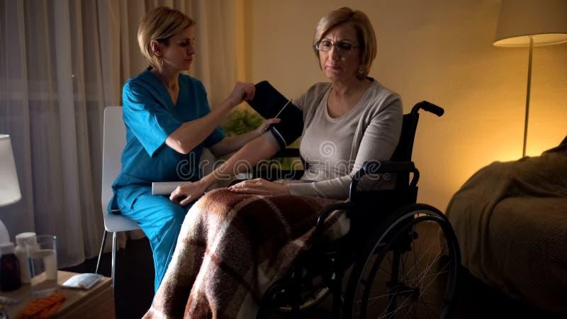 Dameverpleegster die vrouwenbloeddruk, hypertensie, oude dag meten hopeloosheid stock foto