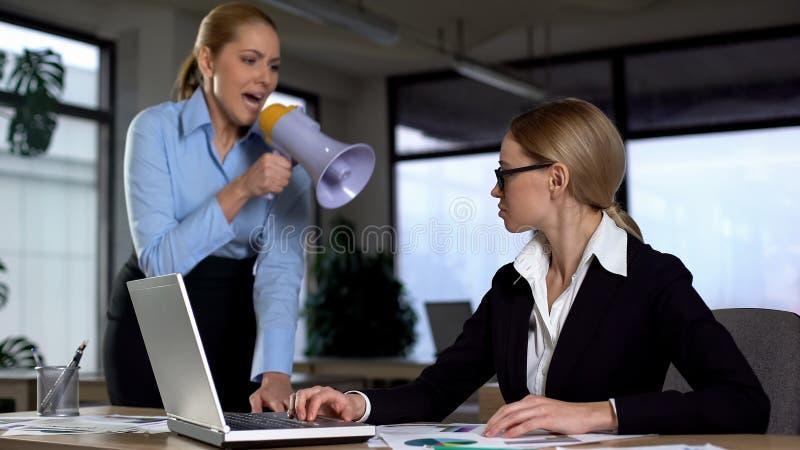 Damewerkgever die met megafoon bij collega, autoritaire leiding schreeuwen stock afbeeldingen