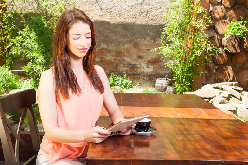 Damezitting buiten met koffie en holdingstablet stock afbeeldingen
