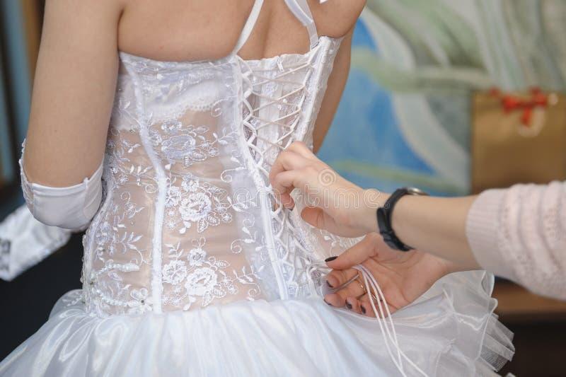 Damigella d'onore che aiuta la sposa che allaccia il suo ritratto del primo piano del vestito immagine stock