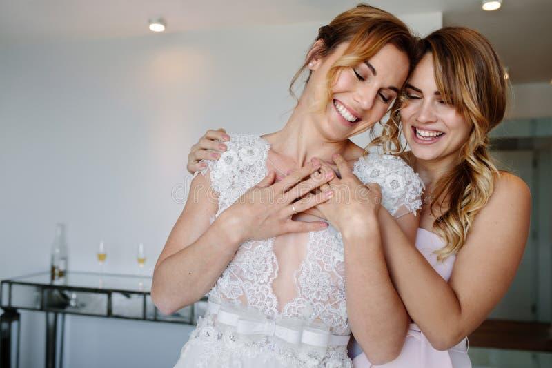 Damigella d'onore che dà un abbraccio tenero alla bella sposa immagine stock