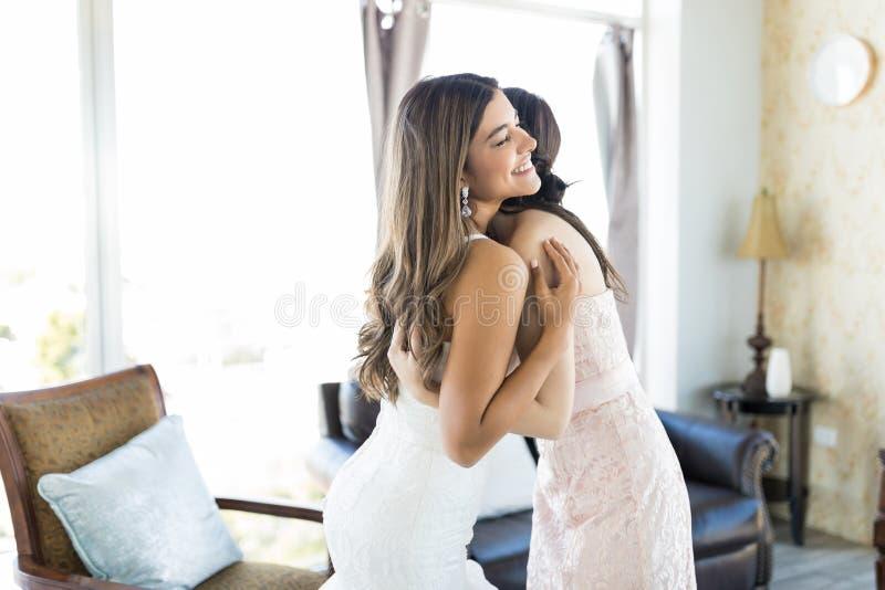 Damigella d'onore che dà un abbraccio tenero alla bella sposa fotografie stock libere da diritti