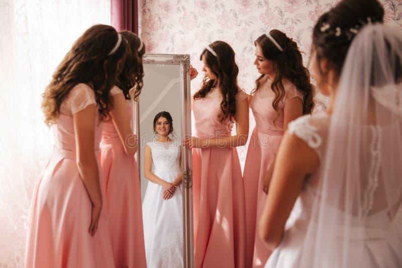Damigella d'onore che fa una pausa lo specchio ed aiutare sposa ad esaminarvi Grande specchio a casa Ragazza felice in stesso ves fotografia stock