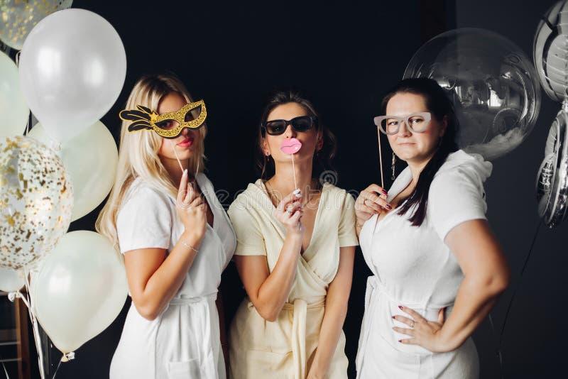 Damigella d'onore che indossa le maschere divertenti che posano con la treccia fotografie stock