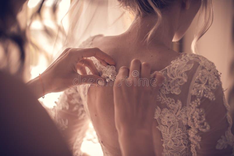Damigella d'onore che lega arco sul vestito da sposa immagine stock libera da diritti