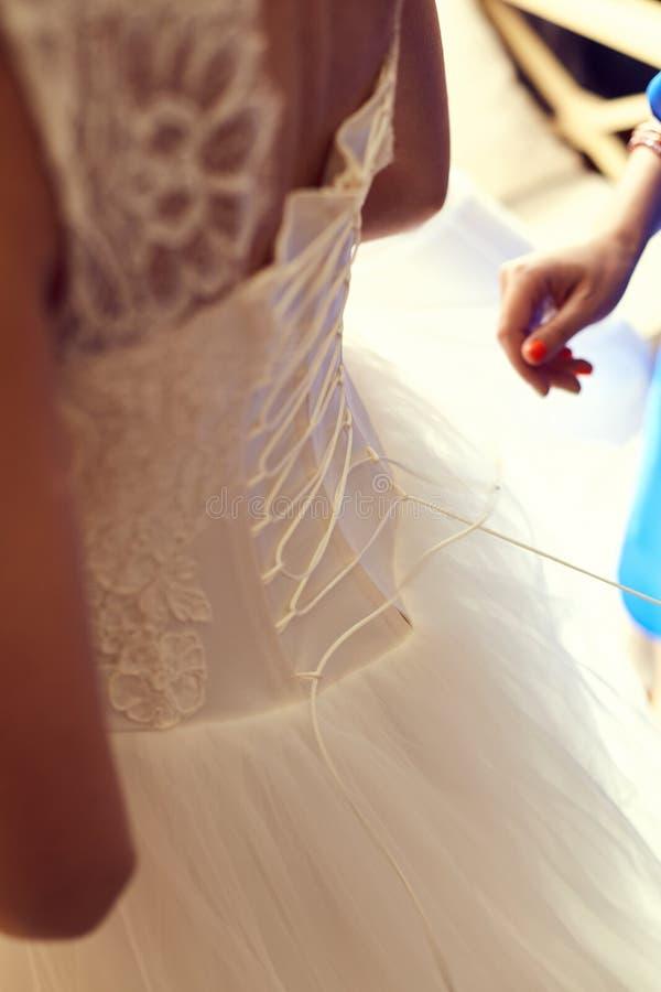 Damigella d'onore che lega arco sul vestito da sposa immagine stock
