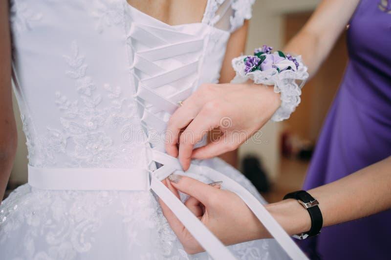 Damigella d'onore che lega arco sul vestito da sposa immagini stock libere da diritti