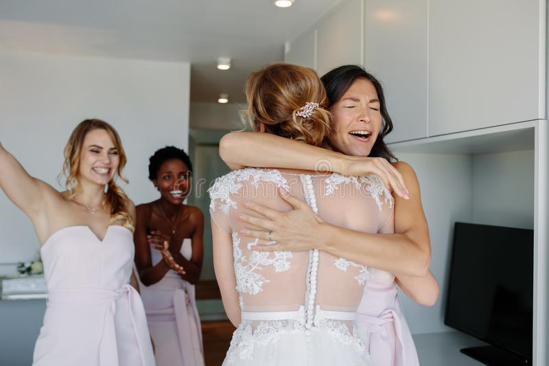 Damigella d'onore che si congratula la sposa prima della cerimonia di nozze fotografia stock