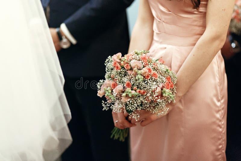Damigella d'onore che tiene mazzo rosa con le rose in chiesa alle nozze immagini stock libere da diritti