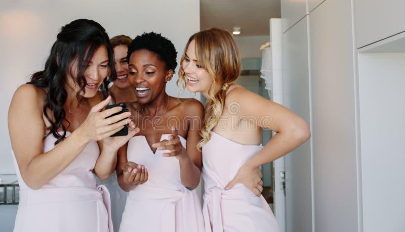 Damigelle d'onore che per mezzo del telefono cellulare sul giorno delle nozze fotografie stock libere da diritti