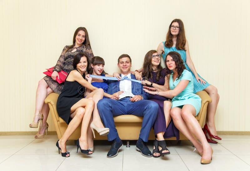 Damigelle d'onore eleganti e sposo alla moda che hanno foto divertenti sul SOF immagine stock
