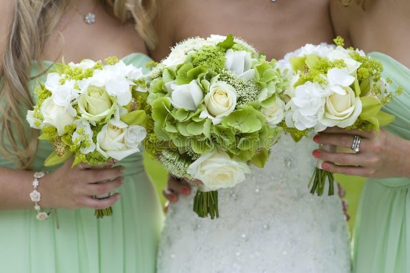 Damigelle d'onore nel verde con il mazzo di cerimonia nuziale immagine stock