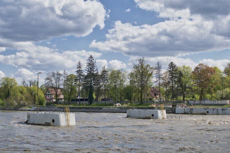 Dammbyggnaden på floden översvämmade vid en våg av högt vatten under vårfloden arkivfoton