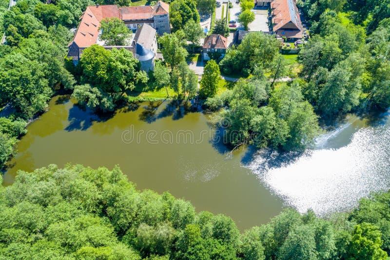 Dammet på den omgav med vallgrav slotten Neuhaus från luften, med buskar och träd, på kanten av byn royaltyfri bild