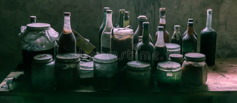 Dammiga gamla glasflaskor och cans med det misstänksamma innehållet arkivfoton