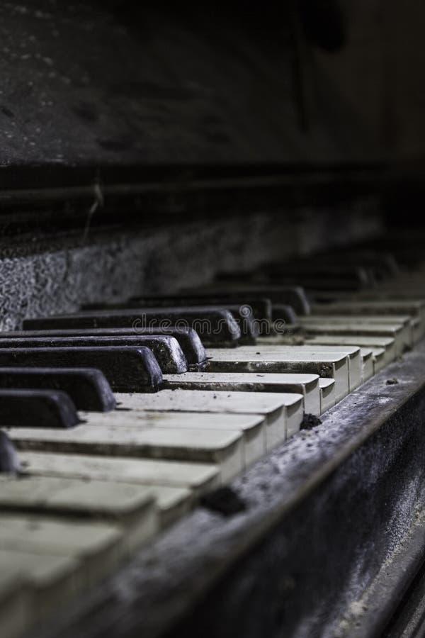 Dammigt gammalt piano med brutna tangenter, slut upp arkivbilder