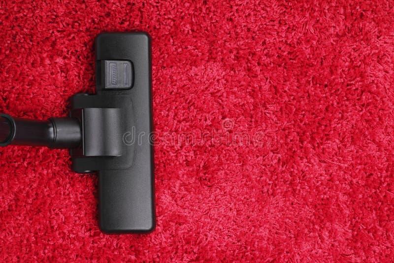 Dammsugare på röd matta fotografering för bildbyråer. Bild