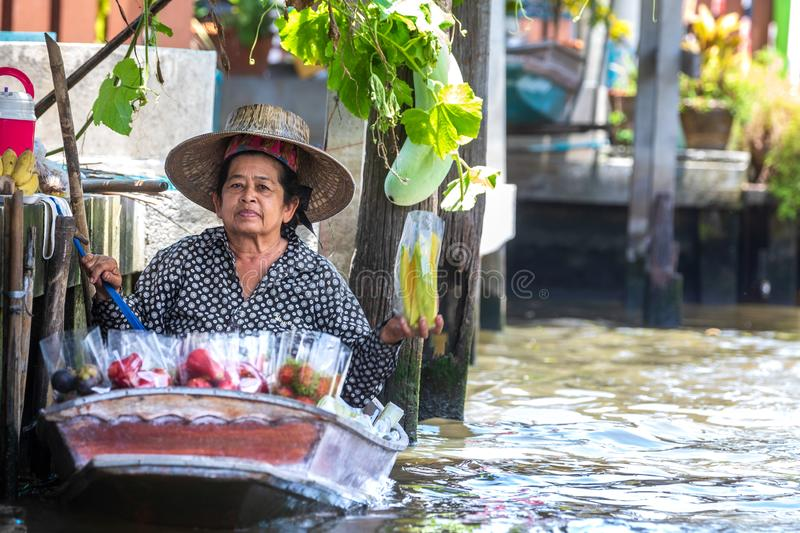 Woman with small boat in the floating market in the Damnoen river in Thailand royalty free stock images