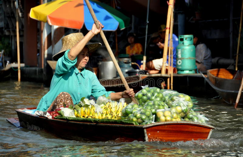 Damnoen Saduak, Thailand: Floating Market Vendor. A woman selling banans, lemons, and limes paddles her boat through the waters of the Floating Market in Damnoen stock photography