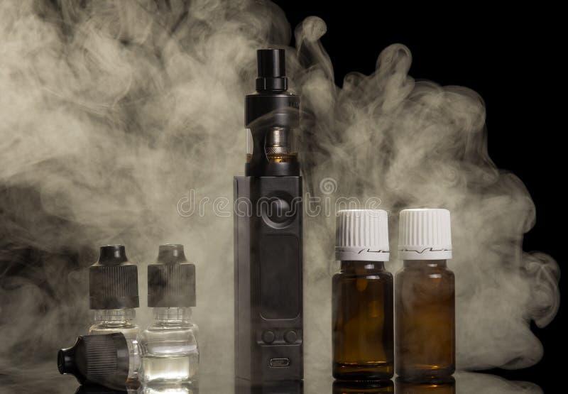 Dampfwolke von einer elektronischen Zigarette, Flaschen Flüssigkeit für das Rauchen, lokalisiert auf Schwarzem stockbilder