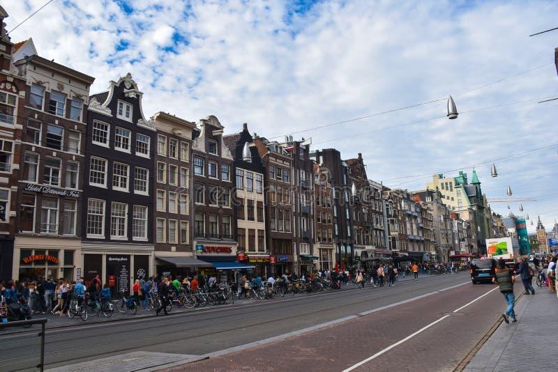 Damrak Gata i mitten av Amsterdam, mellan den centrala drevstationen och fördämningfyrkanten royaltyfri bild