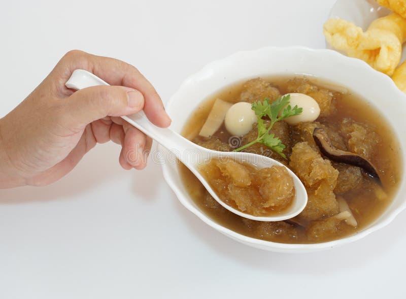 Dams hand genom att använda en sked för att kamma hem soppa för kinesisk stil eller den bräserade fiskmawen i röd sky royaltyfri bild