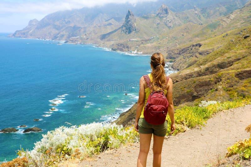 Damturist med ett ryggsäckanseende på berget att tycka om det härliga landskapet av den Tenerife ön royaltyfri foto