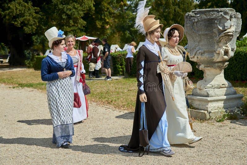 Damy i dżentelmeny w dziejowych kostiumach od Napoleon Bonaparte epoki spacer w parku zdjęcie stock