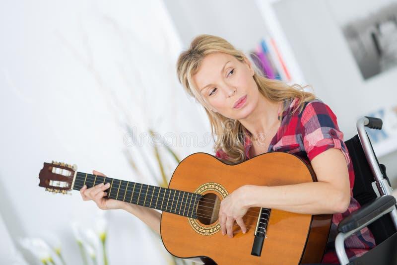 Damy kobieta musican na wózku inwalidzkim bawić się gitarę w domu zdjęcie royalty free