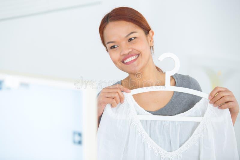 Damy mienie odziewa przeciw cia?u i patrze? w lustrze obrazy stock