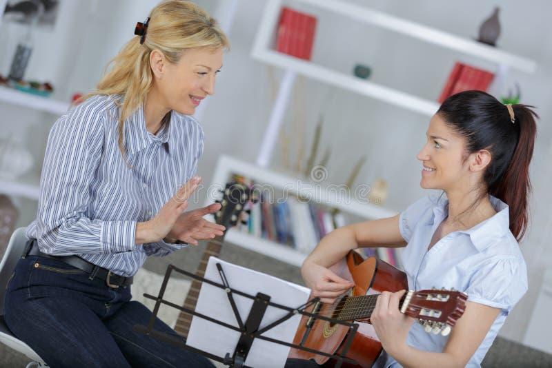 Damy nauczania młoda kobieta dlaczego bawić się gitarę obrazy royalty free