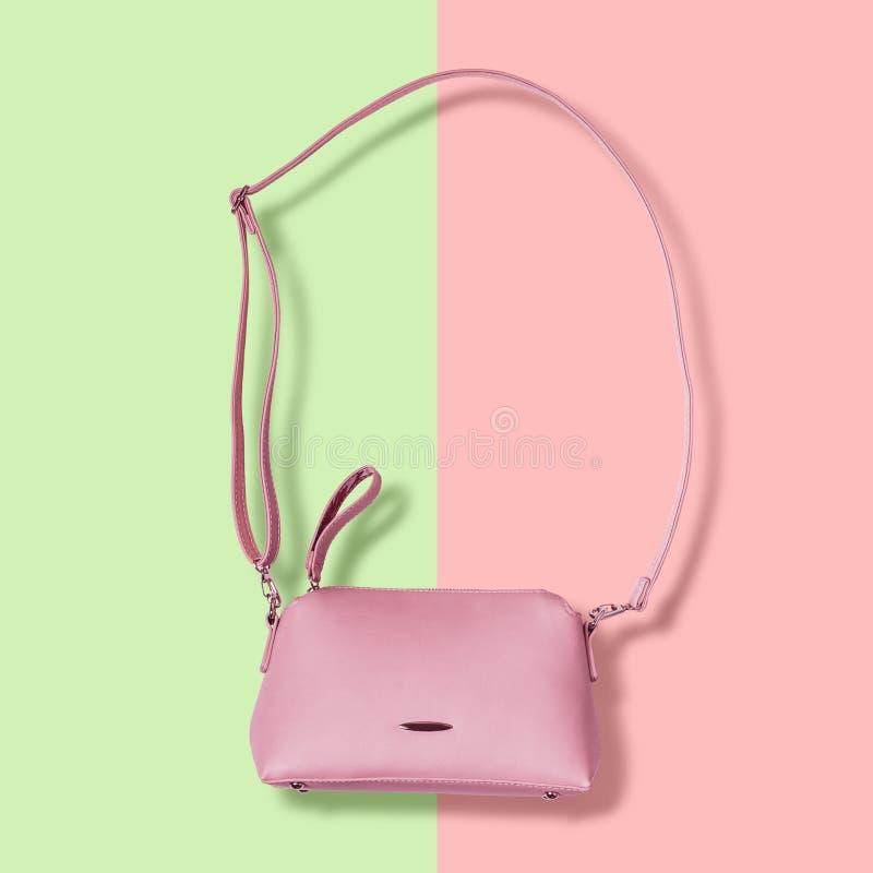 Damy różowią pastelową torebkę z długą patką na różowym tle zdjęcie stock