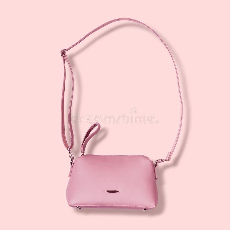 Damy różowią pastelową torebkę z długą patką na różowym tle obraz stock
