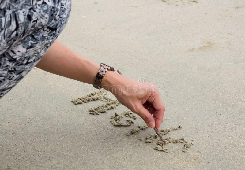 Damy ` s ręki writing słowa ` ` na piasku przy plażą CZEŚĆ obraz stock