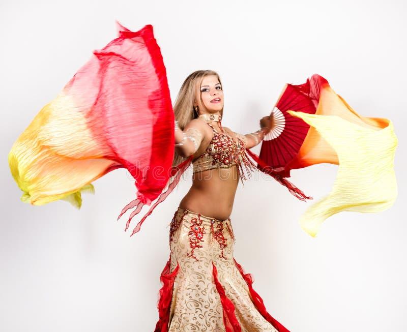 A dança árabe com fãs e fitas executou por uma mulher gorda bonita foto de stock royalty free