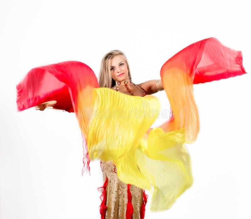 A dança árabe com fãs e fitas executou por uma mulher gorda bonita imagens de stock