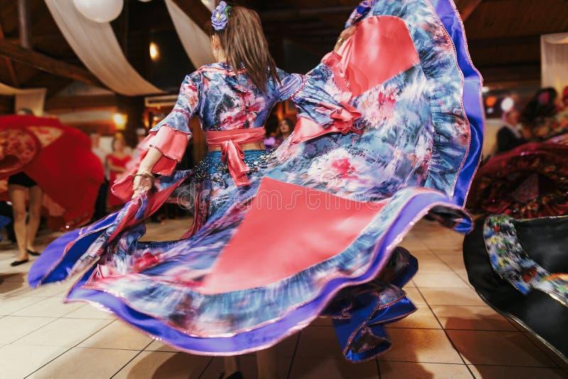 Dança aciganada bonita das meninas no vestido floral azul tradicional no copo de água no restaurante Mulher que executa a dança d imagem de stock