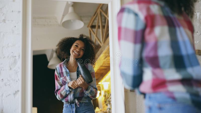 Dança afro-americano engraçada encaracolado da menina e canto com o secador de cabelo na frente do espelho em casa imagens de stock