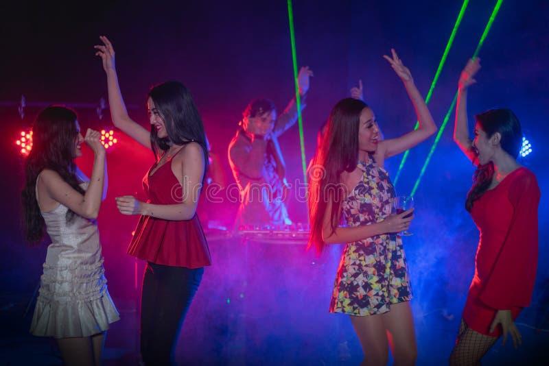A dança alegre dos jovens no partido da noite, DJ misturou a música em foto de stock