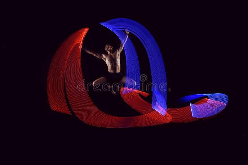 Dança atrativa do bailado do homem com efeito das luzes de incandescência imagens de stock