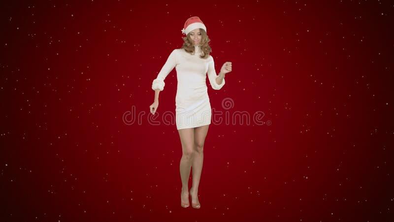 Dança atrativa nova da mulher dos feriados do Natal no fundo vermelho com neve fotografia de stock